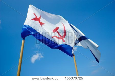 Two flags on background of blue sky. Naval flag of the USSR - red star, hammer and sickle. And Naval flag of Russia. Sevastopol. Crimea