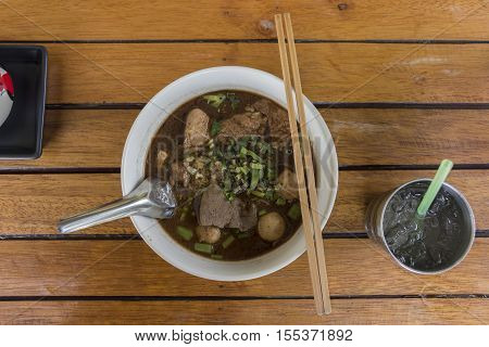 asian noodle soup with pork meatball with fresh vegetable on wood table vintage style, simply food, street food, hot and spicy noodle soup, asian food /Thailand style noodles.