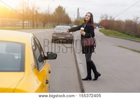 Smiling brunette with long hair stop yellow taxi near road in autumn