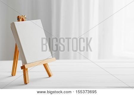 Empty canvas on easel on white wooden desk.