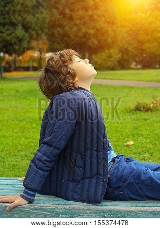 preteen handsome boy sunbathing in autumn bark close up photo