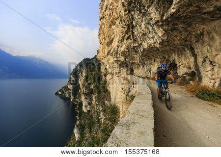 Mountain biking at sunrise man over Lake Garda on path Sentiero della Ponale, Riva del Garda, Italy