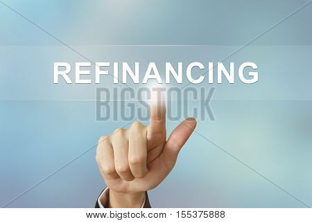 business hand pushing refinancing button on blurred background