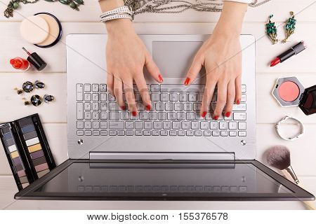 fashion blogger concept - woman with red polished nails working on laptop
