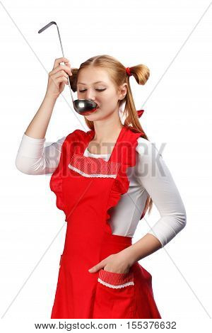 Young beautiful attractive housewife in bright red apron with funny ponytails tasting meal from ladle isolated on white background.