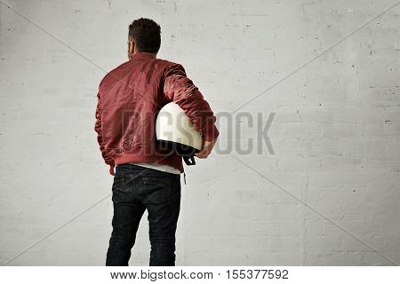Young pilot in jeans, shiny nylon burgundy bomber jacket and a round white helmet under his arm shot from the back against white wall background