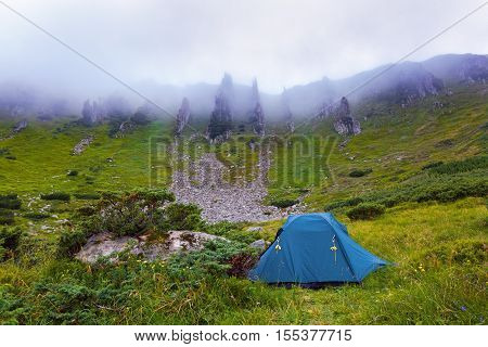 A solitary tourist tent stands on a meadow and around headlong rocky mountains and dense fog on a summer morning.