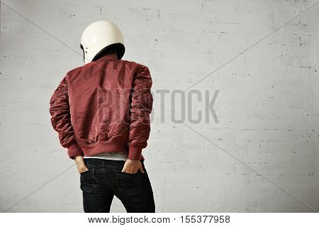 Young motorcyclist in white helmet and red nylon jacket shot from the back with his hands in the back pockets of his jeans in a studio with white walls.