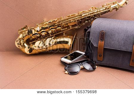 Saxophonist and accessories for travel on rustic wooden background