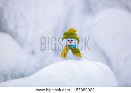 Fairytale character the snowman in hat and scarf is standing on fascinating fluffy snow near the hill and around there are frozen textured patterns.