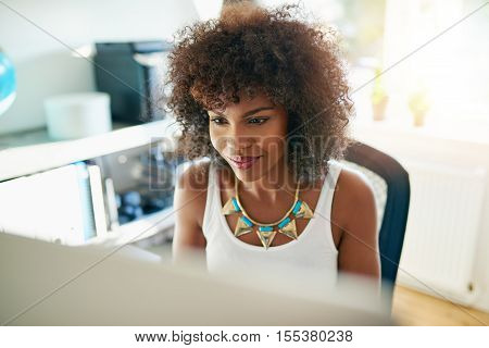 Attractive young African American woman working on a large desktop computer monitor in a bright sunny office reading the screen with a smile