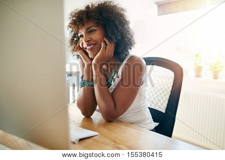 Happy young businesswoman working from home in a new start-up business smiling with pleasure as she reads information on her computer monitor