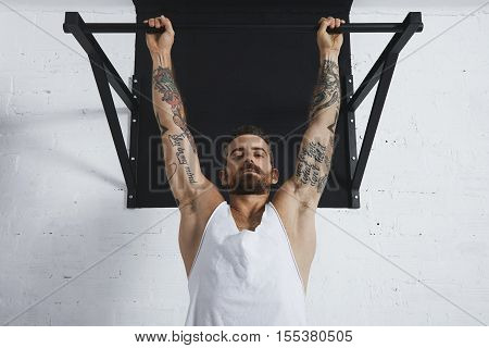 Strong tattooed in white unlabeled tank t-shirt male athlete shows calisthenic moves close up of classic pullup Hanging on pull bar