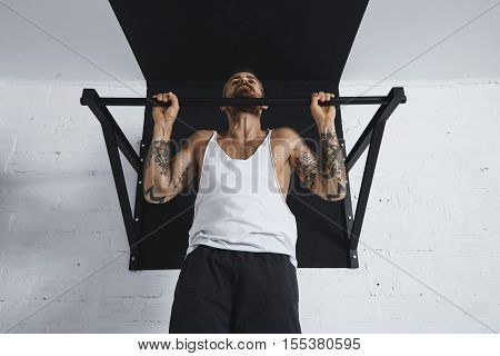 Strong tattooed in white unlabeled tank t-shirt male athlete shows calisthenic moves close up of classic pullup Holding on top of pull bar