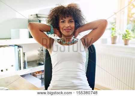 Relaxed confident young African businesswoman leaning back in her chair with her hands clasped behind her neck smiling at the camera in a high key office