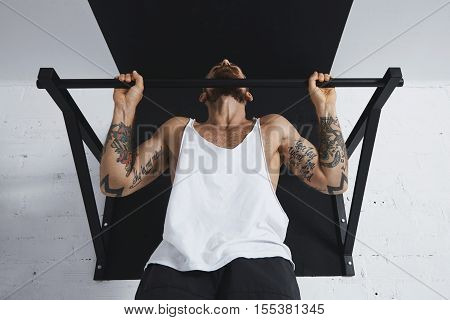 Front view on muscular male athlete in white blank tank t-shirt showing calisthenic moves Pull up with normal classic wide grip on pullbar, holding on top