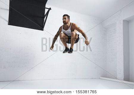 Bearded and tattooed young male athlete shows calisthenic moves High jumps in air, isolated in white room of fitness center