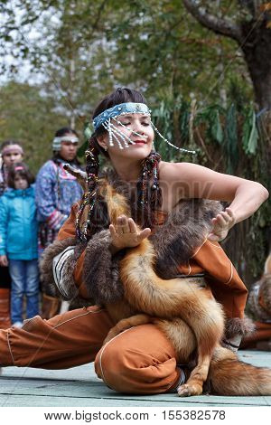 KAMCHATKA PENINSULA RUSSIA - SEP 14 2013: Public concert on Itelmen national holiday of thanksgiving nature Alhalalalay. Expression young woman (ensemble Northern Dawns) dancing in clothing aborigine of Kamchatka.