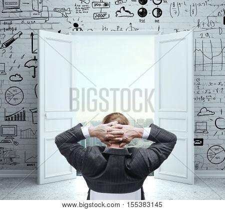 Back view of relaxing young man in suit looking at open door with city view in interior with creative business sketch on white brick wall. Success concept