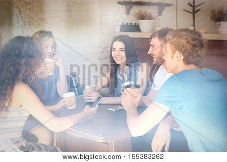 Happy friends drinking coffee in cafe. View through window glass effect.