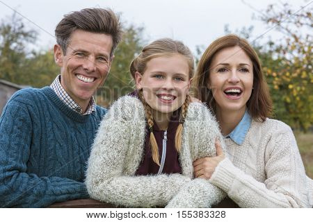 Portrait shot of an attractive, successful and happy family, man, woman, girl child, mother, father and daughter outside in Fall or Autumn
