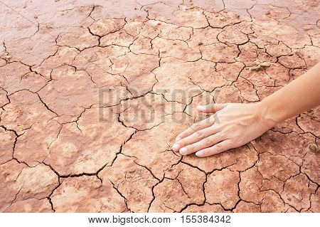 Hand with dried soil in arid season.