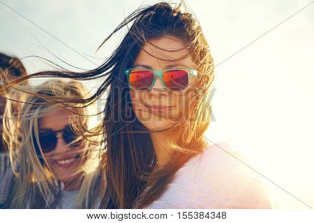 Two gorgeous trendy young women enjoying the breze on a hot summer day standing in their sunglasses smiling at the camera close up head shot