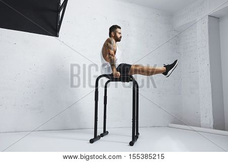 Strong tattooed in white unlabeled tank t-shirt male athlete shows calisthenic moves Holding L Sit position on parallel bars