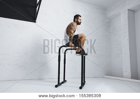 Strong tattooed in white unlabeled tank t-shirt male athlete shows calisthenic moves Kick out L Sit move or tucked on parallel bars
