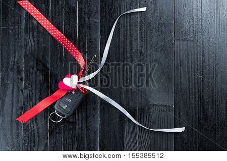 Cark key with a red ribbon adn a heart on black wooden table. Giving present or gift for valentine's day or christmas.