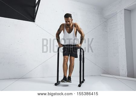 Strong tattooed in white unlabeled tank t-shirt male athlete shows calisthenic moves Straight dips move one, holding on one of parallel bars
