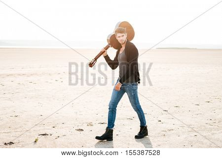 Full length portrait of a young casual man walking at the beach and holding guitar on his shoulder