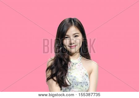Asian woman smiling with dimple long hair black eyes on pastel pink background