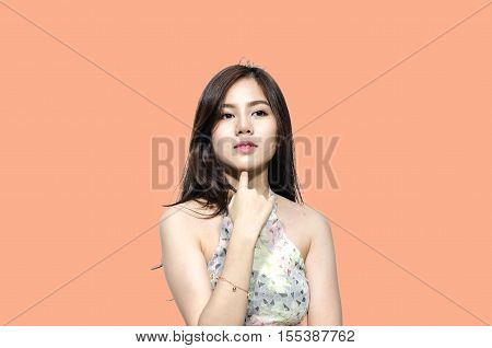 Asian woman smiling with dimple long hair black eyes on orange background