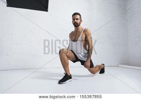 Strong tattooed in white unlabeled tank t-shirt male athlete shows calisthenic moves Lunges, looking at camera