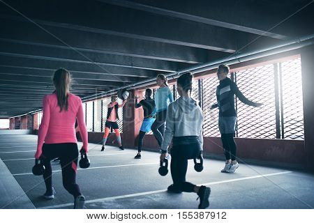 Group of people exercising using weights and skipping ropes wearing sportswear