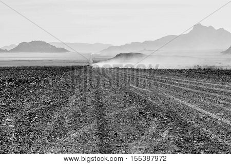 Desert Highway in Southern Namibia showing the gravel road and dust from cars ahead