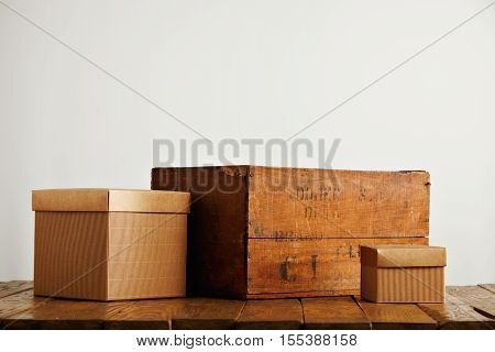 Two new blank brown boxes next to a rustic vintage wine crate in a studio with white walls