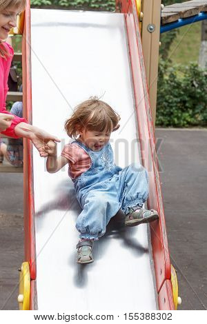 Baby riding at hutches at the playground with disheveled hair