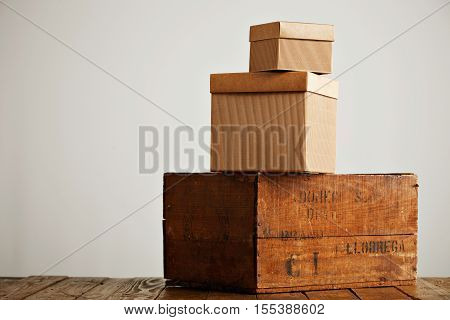 Brown boxes of different sizes and textures arranged in a pyramid on top of a rustic wooden table isolated on white