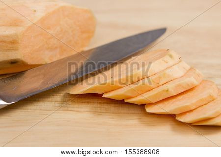 Sliced sweet potato A sweet potato being sliced on a wooden chopping board