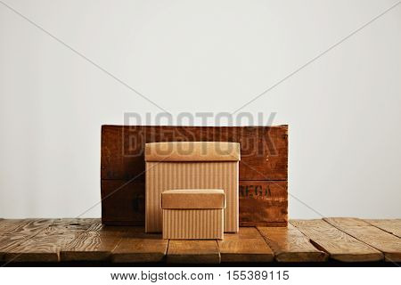 New beige cardboard boxes contrasted against a vintage wine crate and a brown rustic table isolated on white