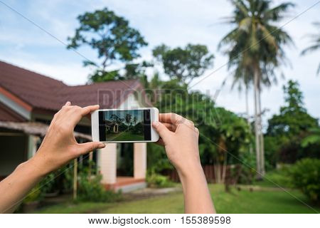 Photographing the house on the phone. Hands with the phone close-up picture. Beautiful house for renting or blog.