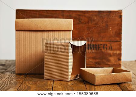 New unlabeled cardboard boxes on a rustic brown wooden table next to a retro wine crate isolated on white