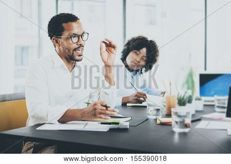 Black african project manager explaning business task in meeting room.Two young entrepreneurs working together in a modern office.Horizontal, blurred background
