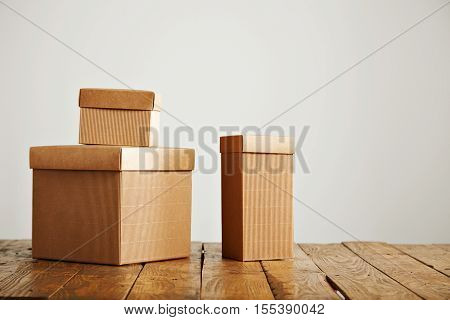 Three different sized beige cardboard boxes arranged on top of a brown rustic table in a studio with white walls