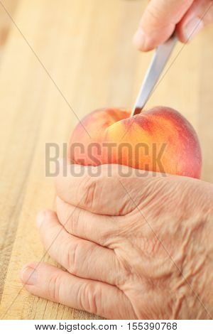 A man cuts into a peach with a paring knife.