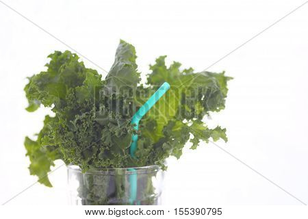 Fresh kale leaves in a drinking glass with a pale blue straw and copy space