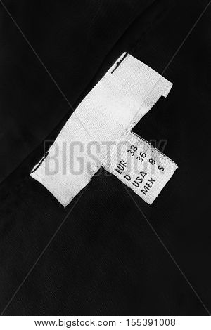 White clothes label on black cloth as a background