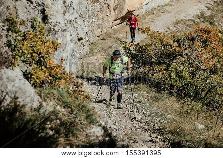 Yalta Russia - October 6 2016: two male athlete with walking poles to walk uphill on background sheer cliff during Crimea mountain marathon